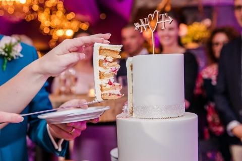 Zdjęcie ślubne momentu cięcia ciasta zamienione w piękny szczegół zdjęcia.