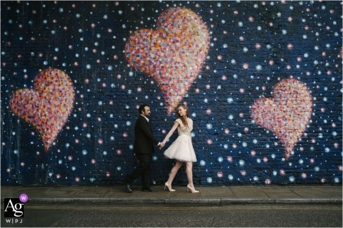 Portrait of bride and Groom walking by Street Art in Borough Market London