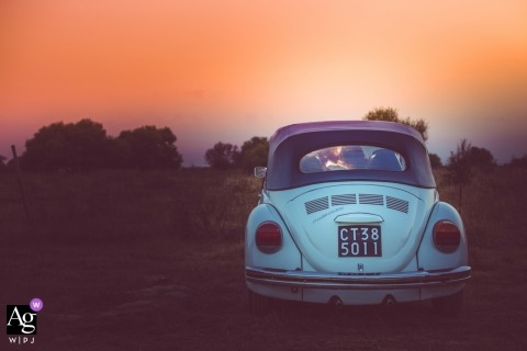 Sicily wedding portrait of the bride and groom at sunset inside a convertible Volkswagen