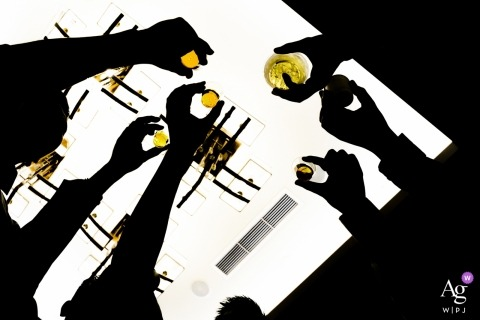 Wedding detail of silhouetted hands reaching over a table to toast  in Fremont, CA