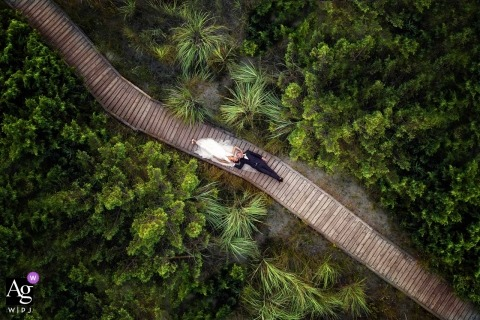Drone wedding portrait of the bride and groom laying on a boardwalk in a forested area in Costa dei Barbari