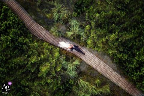 Drone portret ślubny pary młodej leżącej na deptaku w zalesionej okolicy w Costa dei Barbari