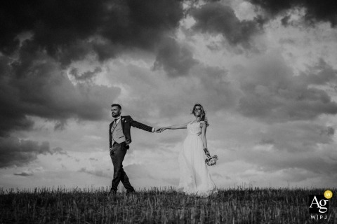 Leonina, Crete Senesuìi wedding portrait of a Couple walking with a storm in the background