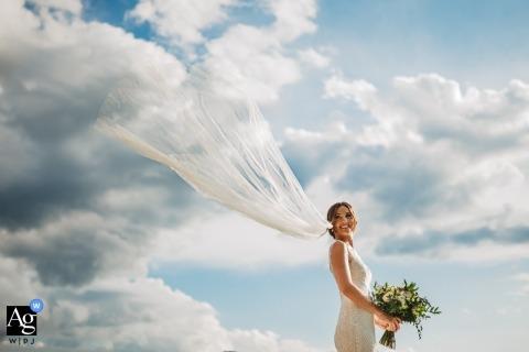 Villa I Cedri, Toscana retrato de boda de la novia y su velo volador en Skys azules y nubes blancas
