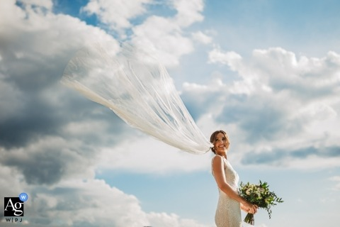Villa I Cedri, Tuscany wedding portrait of the bride and her flying veil in blue Skys and white clouds
