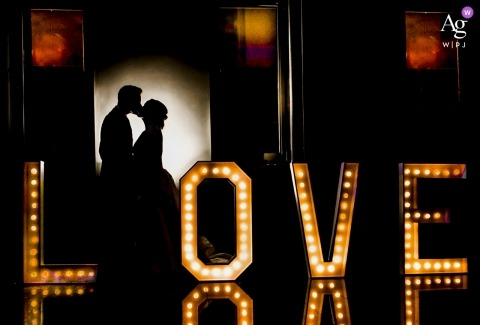 Wedding Portrait of the bride and groom with LOVE in lights at a restaurant in Almería Spain