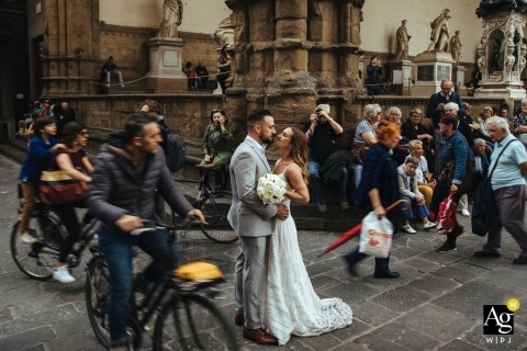 Wedding day portrait of a couple as they kiss on a busy Florence street