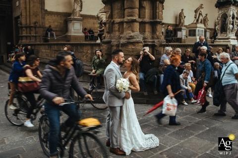 Hochzeitstagporträt eines Paares, wie sie auf einer verkehrsreichen Florenz-Straße küssen