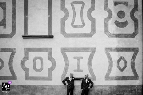 Villa le Maschere wedding portrait of two grooms against a decorated wall.