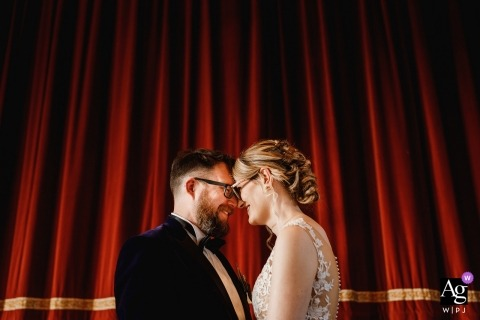 Guiseley Theatre wedding day portrait of a bride and groom standing by a theatre curtain