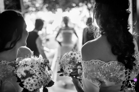 Germany wedding photographer creates an image of the entrance of the bride, from the perspective of the bridesmaids bouquets