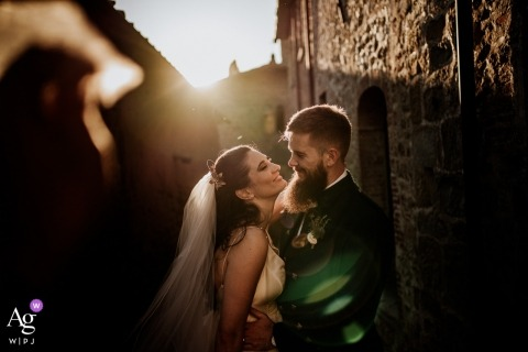 Castello di Gargonza wedding day portrait of a couple  as they smile in the framing inside the small street with a sun flare