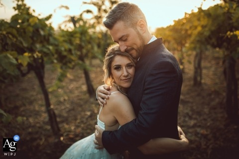 Artistic wedding day portrait of the bride and groom holding each other amongst the grape vines at Valle Dell'Aquila