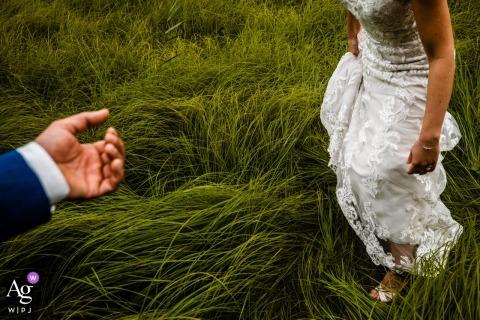 Photographe de mariage néerlandais capture un détail du marié prêtant main-forte à la mariée
