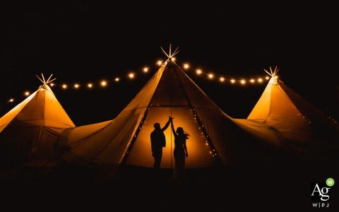 Porthilly Farm, Cornwall Wedding Venue Picture | Silhouettes of the reception dancers against the tipi