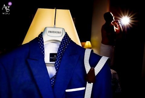 Hochzeitsdetail des Anzugs und der Hosenträger des Bräutigams, wenn der Bräutigam im Hintergrund fertig wird
