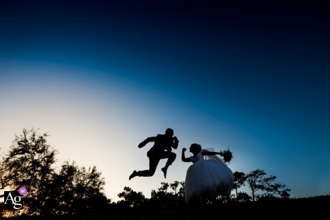 Vieux Boucaut, France fun and artistic wedding portrait of a silhouetted bride dancing and the groom jumping