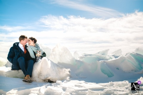 Bride and groom sit for a rest on the icy shores of Lake Ontario for a wedding portrait