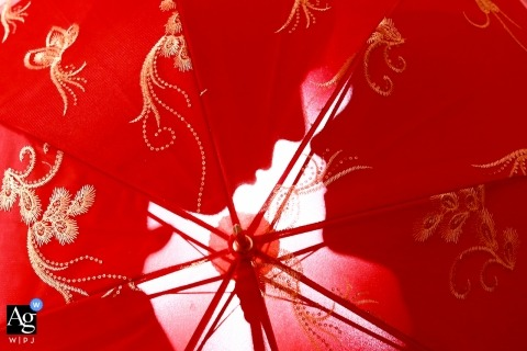 China wedding detail of a red embroidered umbrella with the silhouette of the bride and groom behind
