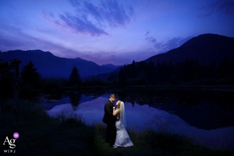 Wedding couple pose together near a pond during twilight as wildfire smoke fills the area at Bruce Spruce Ranch