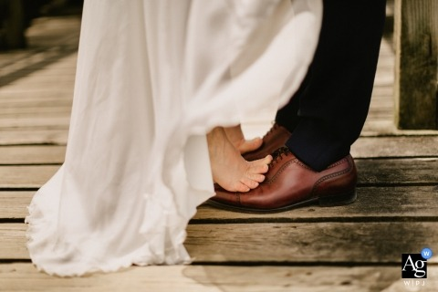 Hossegor, France wedding detail picture of the feet of the bride and groom kissing after a walk on the beach
