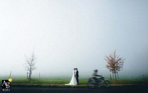 Muri, Aargau, Switzerland wedding portrait in the autumn fog, as a motorcyclist drives by