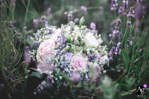 Wedding detail image of a lavender bridal bouquet in a small lavender garden field