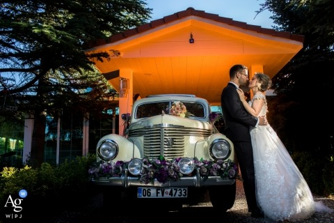 Couple standing next to a vintage car is looking each other for a wedding portrait at İncek Garden, Ankara