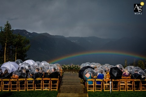Outdoor wedding ceremony image in Colorado of guests as they wait out rain and get a rainbow as a reward as they wait for ceremony to start