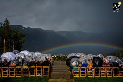 Im Freienhochzeitszeremoniebild in Colorado der Gäste, während sie heraus Regen warten und einen Regenbogen als Belohnung erhalten, während sie warten, bis Zeremonie beginnt