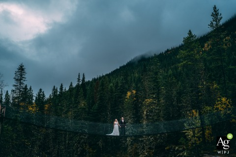Mount Robson Provincial Park, BC, Canada Bride and Groom photo of them holding the hands on the suspension bridge.
