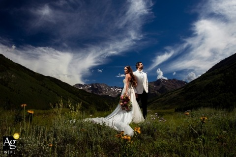 Boulder bride and groom portrait in an open field with flowers