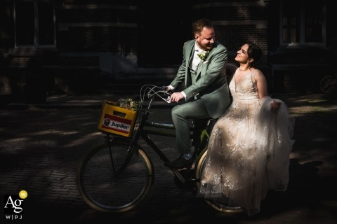 Bovendonk, Hoeven Venue wedding day portrait of the bride and groom coming to the location on a bike