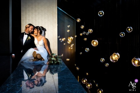 Bride is sitting on a platform and groom is next to her close to gallery space with lamps hanging from the ceiling at the Hilton Ankara