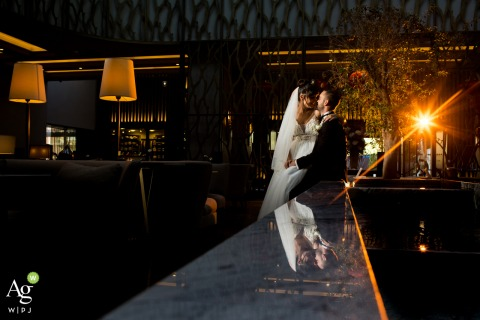 Hilton Ankara wedding venue photography | Portrait of the Groom sitting just the edge of a fountain at a lobby of a hotel and bride is next to him