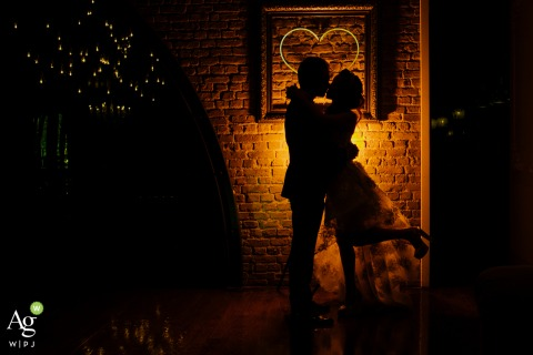 Wyndham Ankara wedding day portrait photo | Silhouette of the couple standing close to a brick wall with a love neon sign