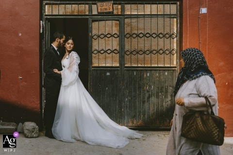 Elderly woman looking curiously to the wedding couple while they are posing in front of her house door for a portrait