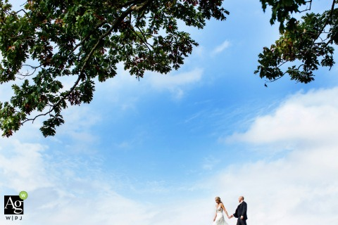 Bear Brook Valley New Jersey Wedding day portrait photo of the bride and groom holding hands and walking under the trees and blue sky