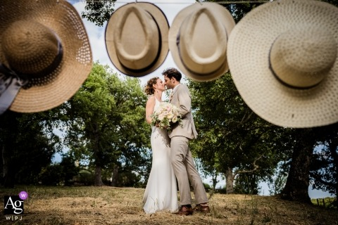 Private villa, Tuscany wedding portraits | Kissing with hats frame