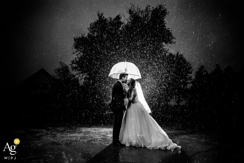 the mora farm wedding venue photography of the bride and groom kissing on the rain
