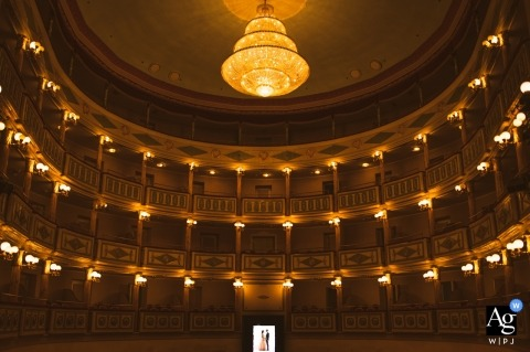 Place of wedding ceremony: Theater in Foggia. Pictures Shot from the stage while groom and bride are lit by sun rays outside the theater.