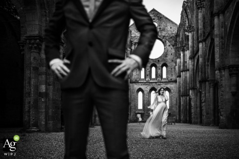 Wedding Photo | San Galgano Abbey, Tuscany, Italy	bride and groom portrait in black and white with some wind.