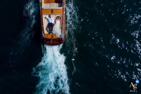 Lake Como, Italy wedding drone photography of the bride and groom on the back of a boat
