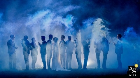Hotel Kasteel de Essenburgh, The Netherlands wedding photographer – Group picture of Wedding couple with the friends. 2 men are running around with smoke flares to create the smoke screen.
