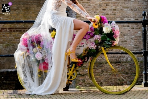 Photographie de mariage aux Pays-Bas, Musée de Gouda | La mariée qui fait du vélo quotidiennement devait prendre une photo sur le vélo jaune, car le jaune était la couleur du thème de leur mariage.