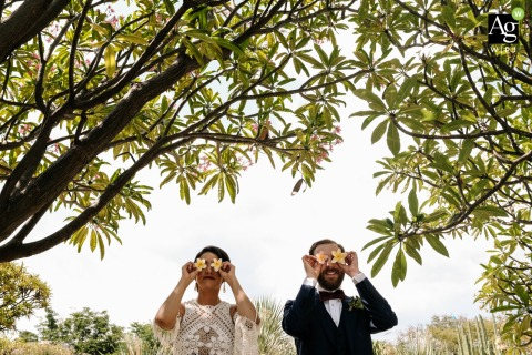 Jardin Etnobotanico, Oaxaca City, Oaxaca, Mexico wedding day portrait of the newlyweds having fun under the trees with flowers