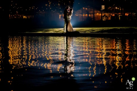 Brasserie Buitenhuis, Valkenburg Wedding Photography | Night time backlit portrait of the wedding couple with water reflection and lights.