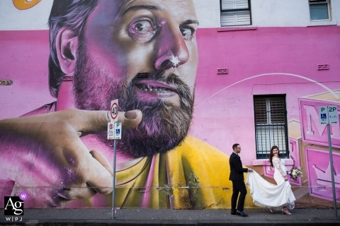 Victoria, Australia Melbourne Bride and groom walking by street art mural for portraits on wedding day.