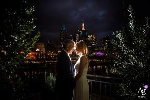 Victoria, Australia Melbourne Bride and groom pose for wedding portrait at night with lights
