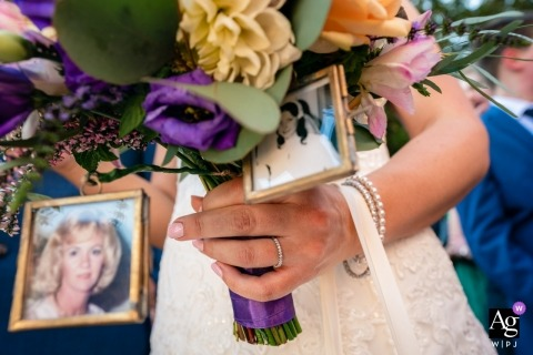 Farnham Castle, Surrey Wedding Detail Photography |	Shot of brides ring, while holding bouquet, photos of deceased relatives in picture frames on bouquet. Unposed.